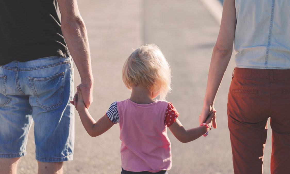 Kind hand in hand met ouders